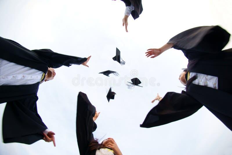 Gelukkige gediplomeerden die hoeden werpen royalty-vrije stock foto