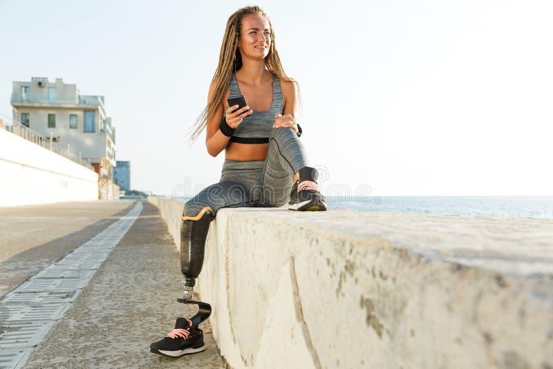 Gelukkige gehandicapte atletenvrouw met prothetisch been stock fotografie