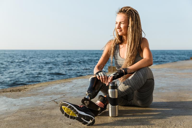 Gelukkige gehandicapte atletenvrouw met prothetisch been stock foto