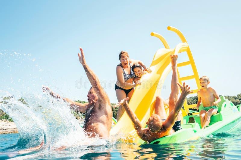 Gelukkige gekke familiehanden omhoog op de drijvende Catamaran van de Speelplaatsdia aangezien zij die van overzeese reis geniete stock foto