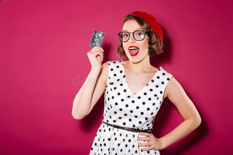 Gelukkige gembervrouw in kleding en oogglazen die creditcard houden stock afbeeldingen