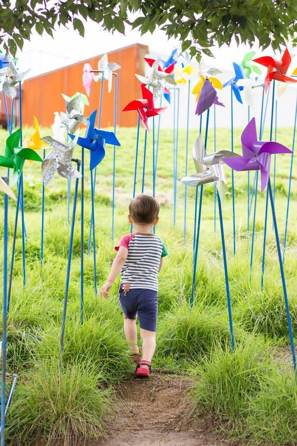 Gelukkige Gemengde gerende Jongen die aan gras lopen hoewel windspinners royalty-vrije stock foto