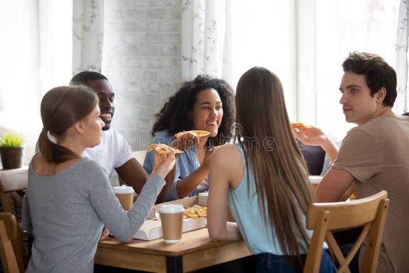 Gelukkige gemengde rasvrienden die pizza in koffie eten stock foto's