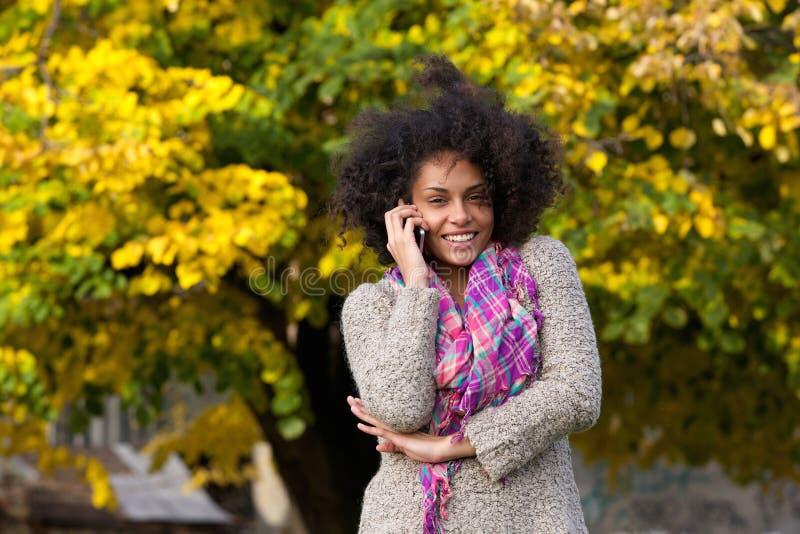 Gelukkige gemengde rasvrouw die op mobiele telefoon in openlucht spreken royalty-vrije stock afbeeldingen