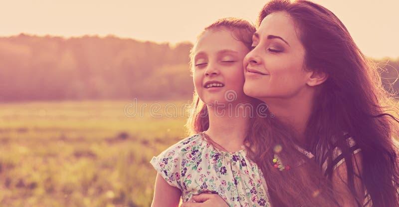 Gelukkige genietende van moeder die haar ontspannend joying jong geitjemeisje koesteren die verse lucht op achtergrond van de zon royalty-vrije stock afbeeldingen