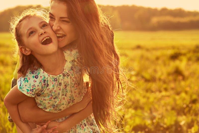 Gelukkige genietende van moeder die haar speels lachend jong geitjemeisje op achtergrond van de zonsondergang de heldere zomer ko stock afbeelding