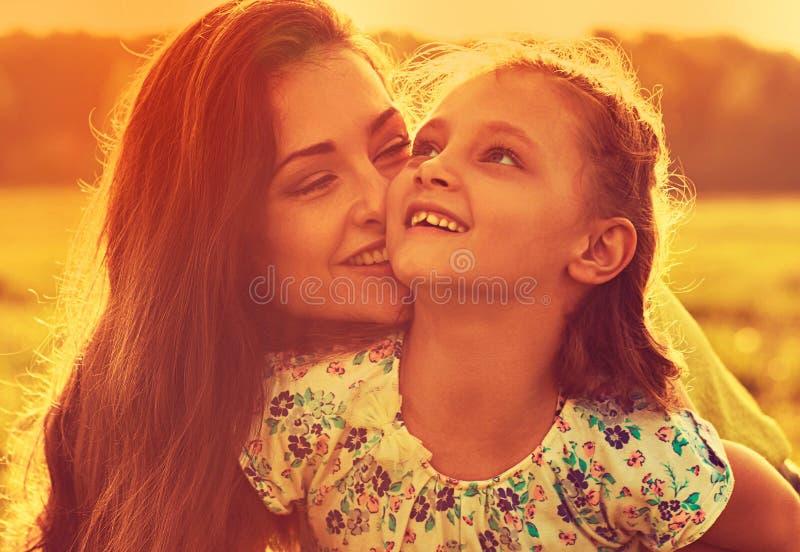 Gelukkige genietende van moeder die haar speels lachend jong geitjemeisje in zonsondergang zonnig licht koesteren op de zomeracht royalty-vrije stock foto's