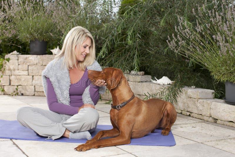 Gelukkige gerijpte vrouw die haar opleiden hond openlucht royalty-vrije stock afbeelding