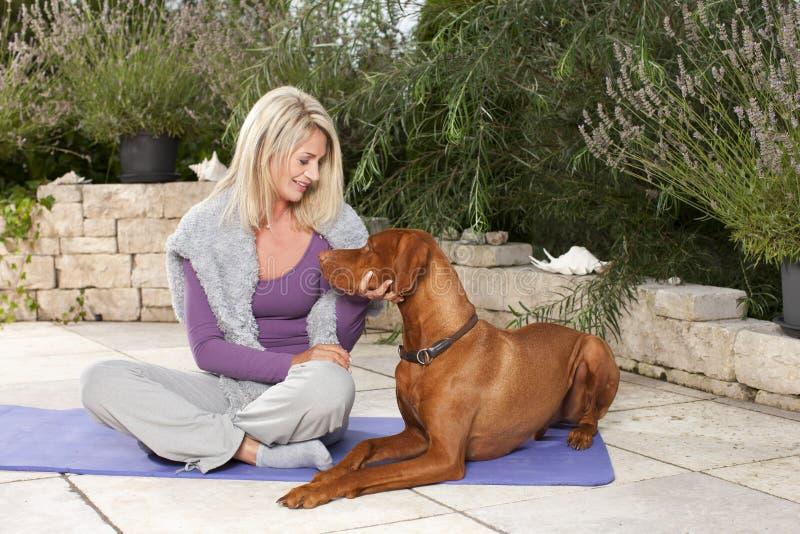 Gelukkige gerijpte vrouw die haar opleiden hond openlucht stock afbeelding