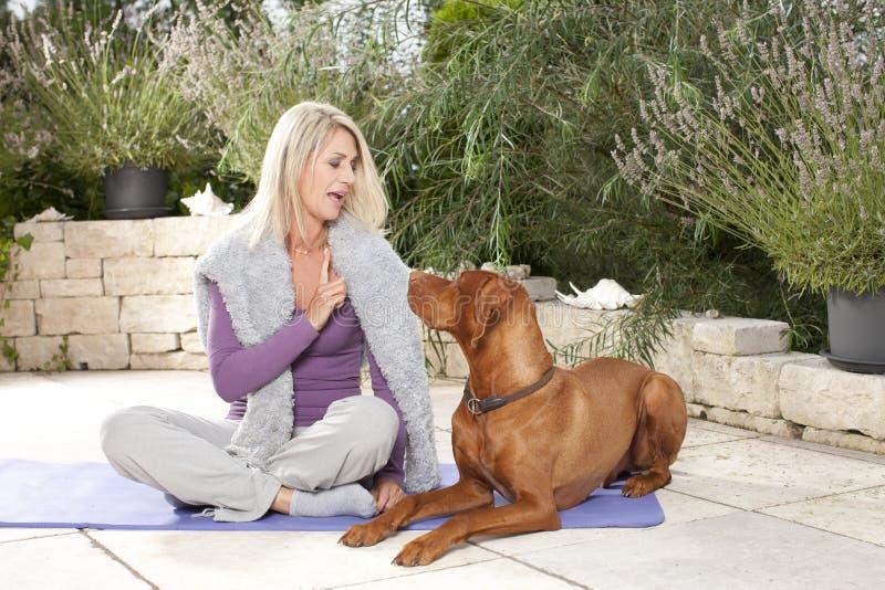 Gelukkige gerijpte vrouw die haar opleiden hond openlucht stock afbeeldingen