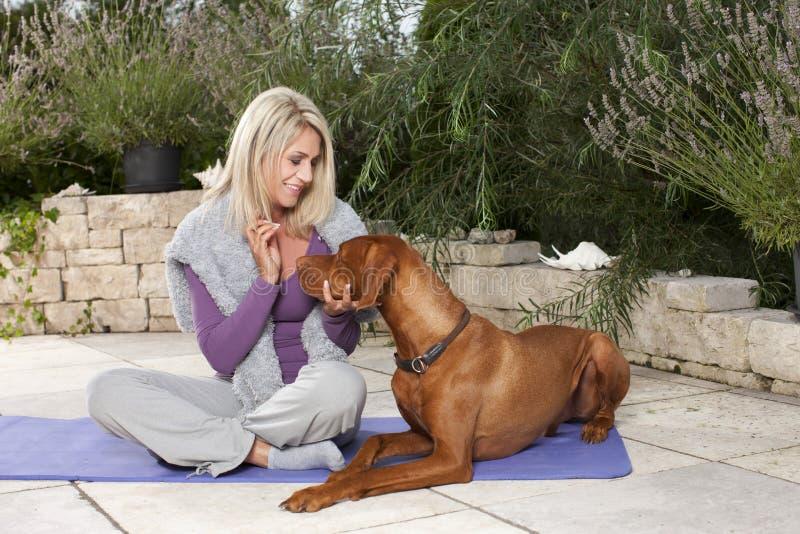 Gelukkige gerijpte vrouw die haar opleiden hond openlucht royalty-vrije stock afbeeldingen