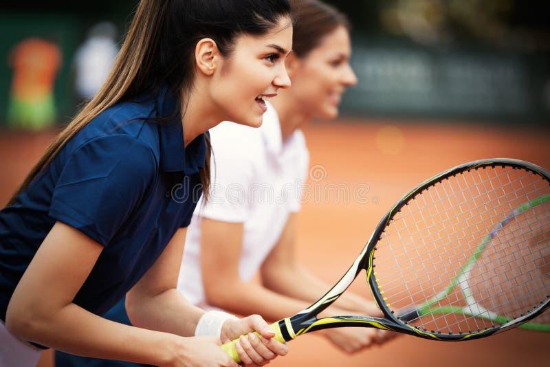 Gelukkige geschikte mensen die tennis samen spelen Het concept van de sport stock afbeelding