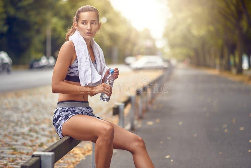 Gelukkige geschikte vrouw die een onderbreking van jogging nemen royalty-vrije stock fotografie