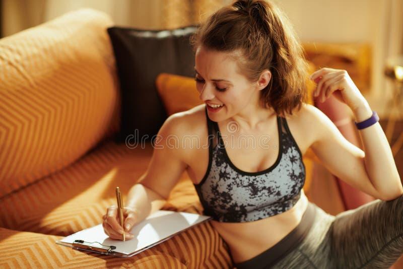 Gelukkige geschikte vrouw met klembord en pen het schrijven geschiktheidsdoelstellingen stock foto