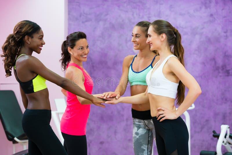 Gelukkige geschikte vrouwen die handen samenbrengen vóór clas van de groepstraining stock afbeelding