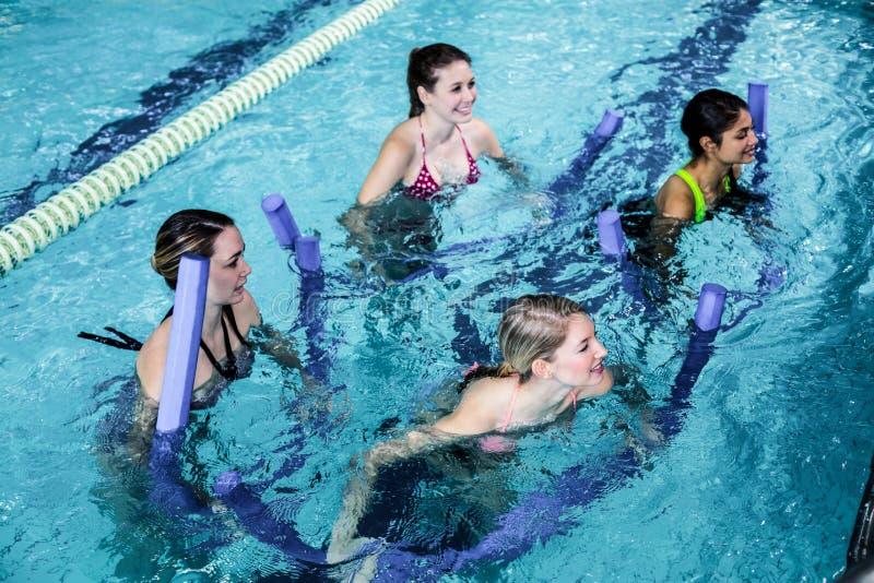 Gelukkige geschiktheidsklasse die aquaaerobics met schuimrollen doen stock fotografie