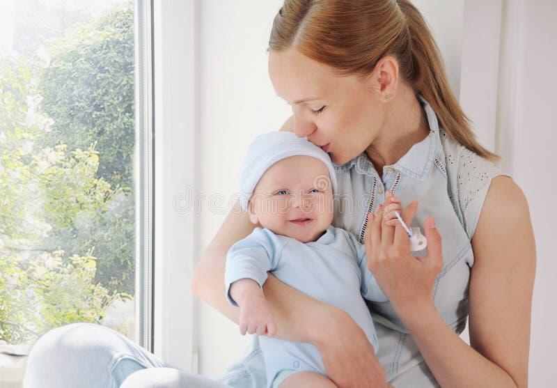Gelukkige gevende moeder die haar leuke pasgeboren babyjongen kussen royalty-vrije stock afbeelding