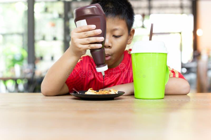 Gelukkige gezichts Aziatische jongen die chocolade op wafels voor ontbijt drukken royalty-vrije stock foto's