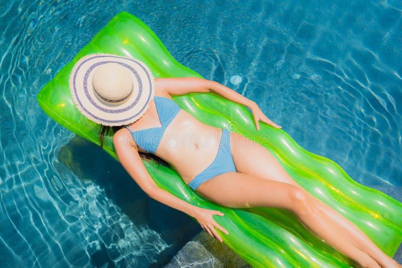 Gelukkige glimlach van de portret ontspant de mooie jonge Aziatische vrouw en vrije tijd in het zwembad stock afbeeldingen