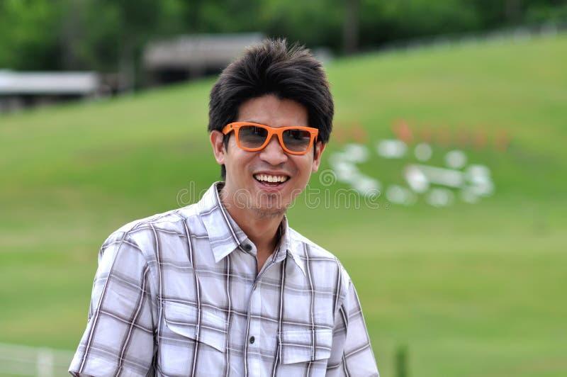 Gelukkige Glimlach van de Zonnebril van de Mens van Azië Thailand de Oranje royalty-vrije stock afbeelding
