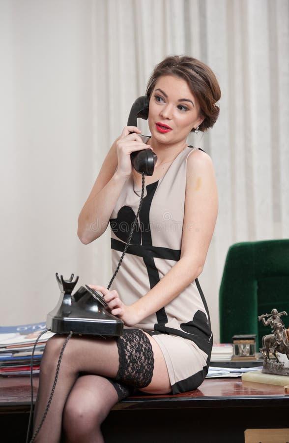 Gelukkige glimlachende aantrekkelijke vrouw die een elegante kleding en zwarte kousen dragen die telefonisch in een bureaulandsch stock afbeelding