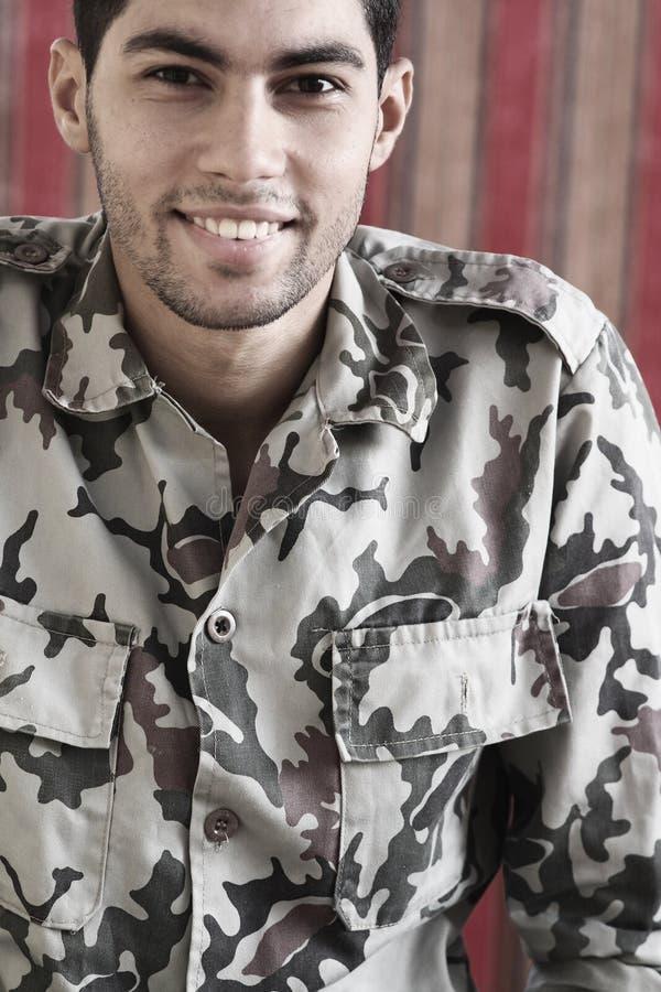 Gelukkige glimlachende Arabische Egyptische jonge mens in militair kostuum stock fotografie