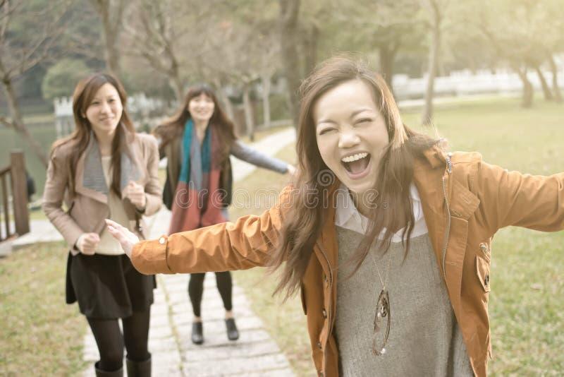 Gelukkige glimlachende Aziatische vrouwen die in het park spelen royalty-vrije stock foto's