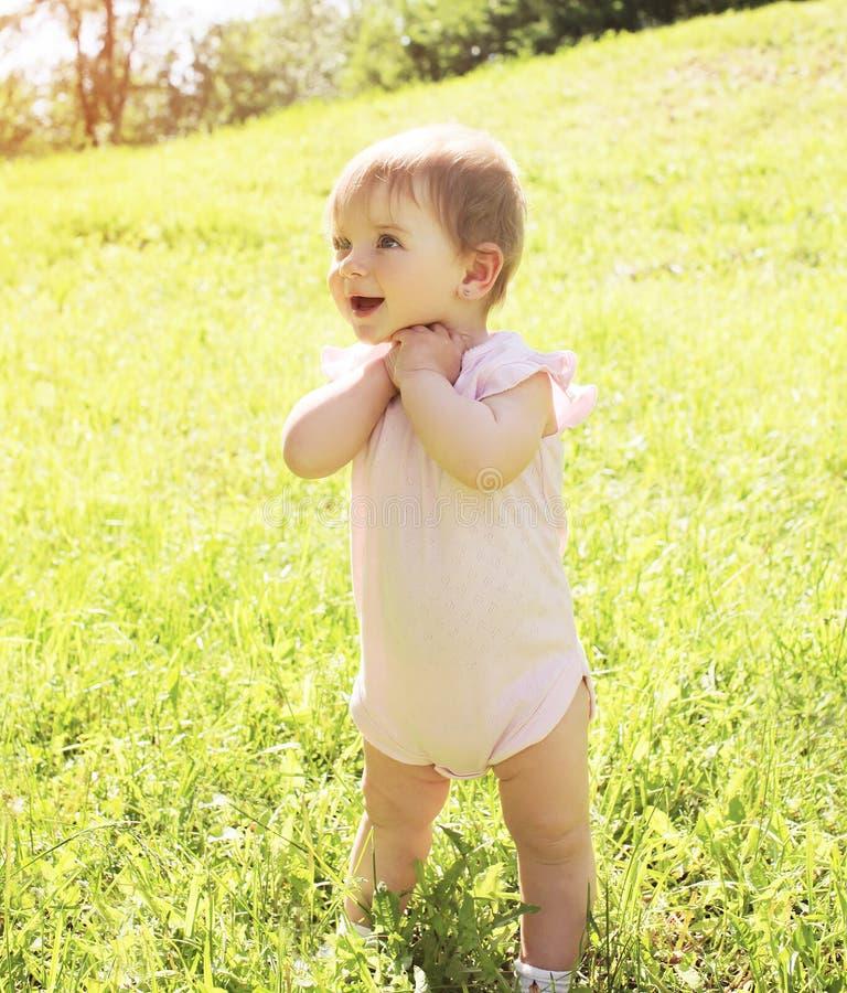 Gelukkige glimlachende baby die zich op gras in de zonnige zomer bevinden royalty-vrije stock afbeeldingen