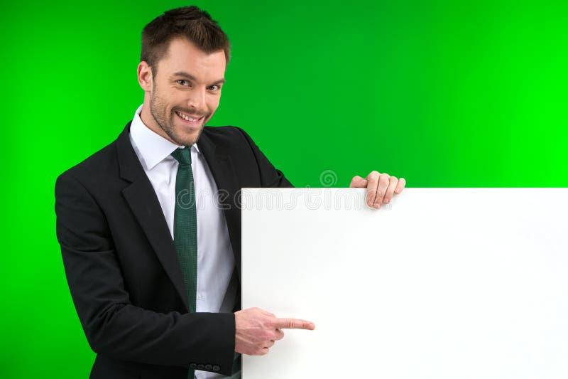 Gelukkige glimlachende bedrijfsmens die leeg uithangbord tonen stock fotografie