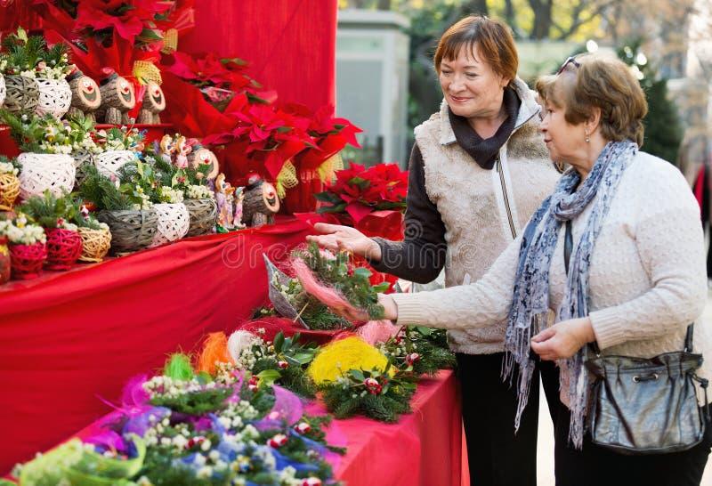 Gelukkige glimlachende bejaarden die bloemensamenstellingen selecteren stock fotografie