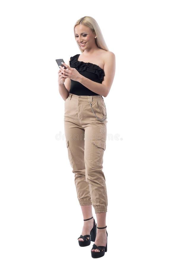 Gelukkige glimlachende blonde modieuze vrouw die mobiel telefoon het typen bericht gebruiken royalty-vrije stock afbeeldingen