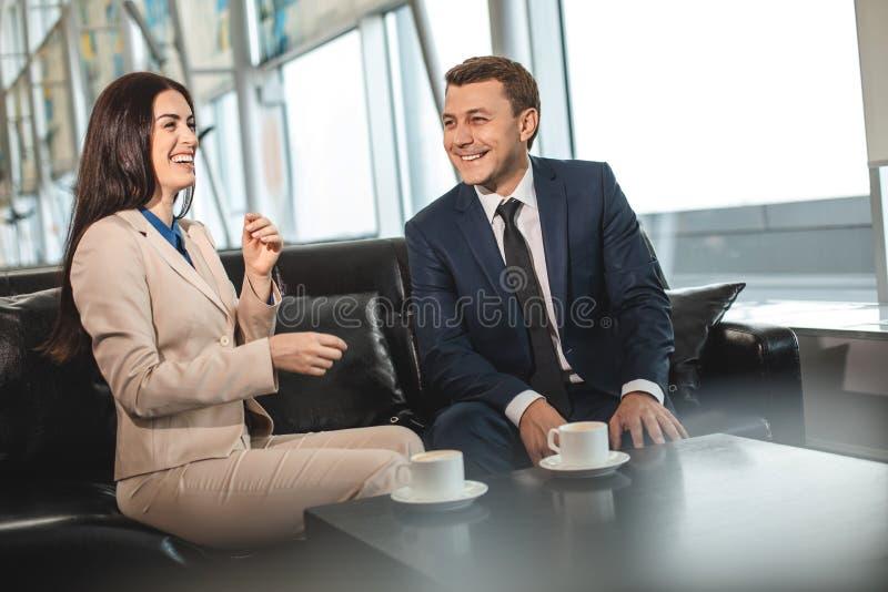Gelukkige glimlachende collega's die op bank in ruimte de plaats bepalen van royalty-vrije stock afbeeldingen