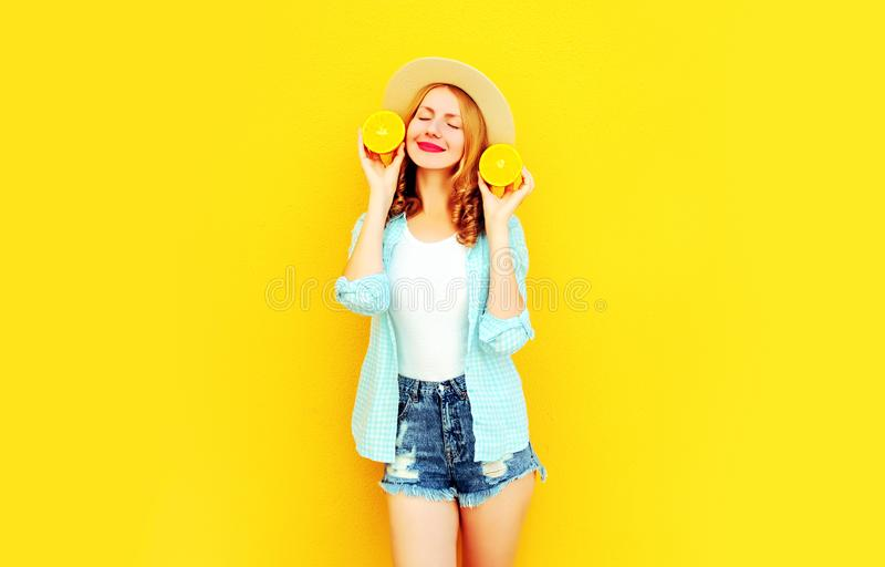 Gelukkige glimlachende de vrouwenholding van het de zomerportret in haar handenplakken van sinaasappel in strohoed, borrels op kl stock foto's