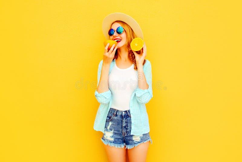 Gelukkige glimlachende de vrouwenholding van het de zomerportret in haar handenplakken van sinaasappel in strohoed, borrels op kl royalty-vrije stock fotografie
