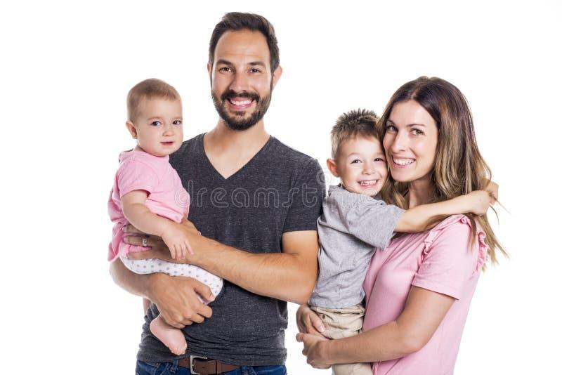 Gelukkige glimlachende die familie van vier op witte achtergrond wordt geïsoleerd stock foto's