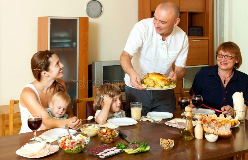Gelukkige glimlachende drie generatiesfamilie die kip met wijn eten stock afbeeldingen