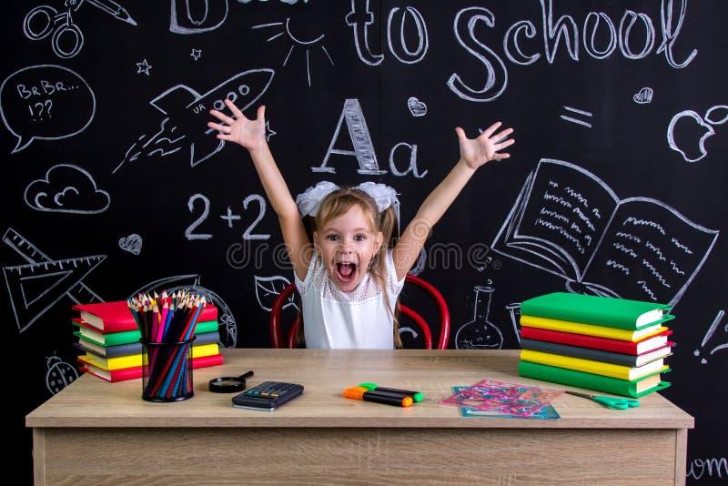 Gelukkige, glimlachende en opgewekte schoolmeisjezitting bij het bureau met beide die omhoog wapens, met schoollevering worden om stock afbeelding