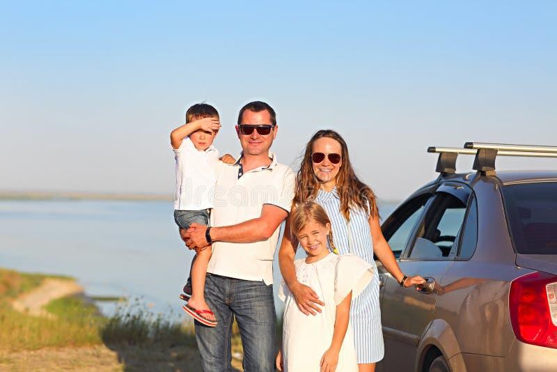 Gelukkige glimlachende familie met twee jonge geitjes door de auto met overzees backgroun stock afbeelding