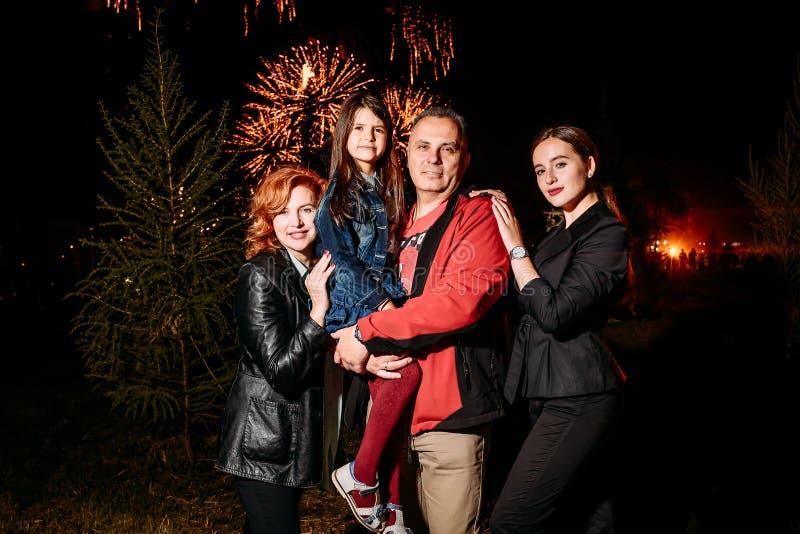 Gelukkige glimlachende familie van vier bij nacht op de achtergrond van vuurwerk royalty-vrije stock afbeelding