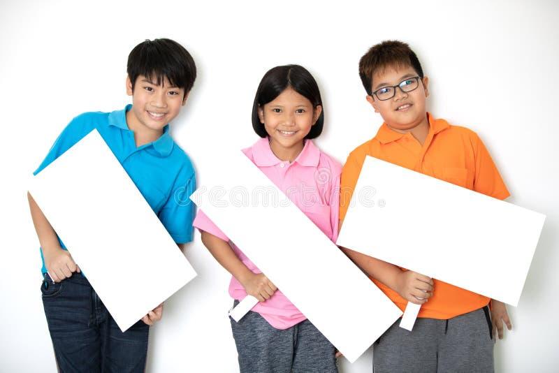 Gelukkige glimlachende groep die jonge geitjes lege aanplakbiljetraad tonen stock foto's