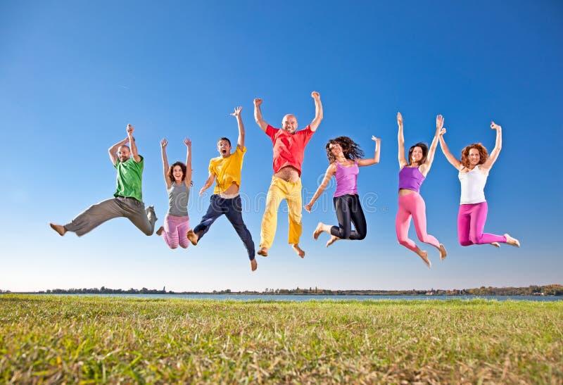 Gelukkige glimlachende groep springende mensen stock afbeeldingen