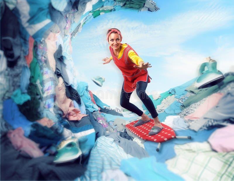 Gelukkige glimlachende huisvrouw die op strijkplank surfen royalty-vrije stock fotografie