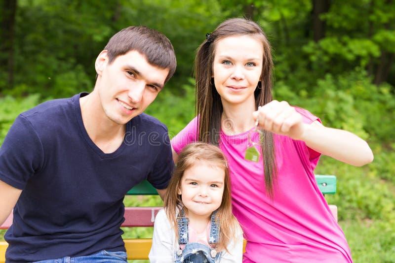 Gelukkige glimlachende jonge familie die sleutel van hun nieuw huis tonen stock afbeeldingen