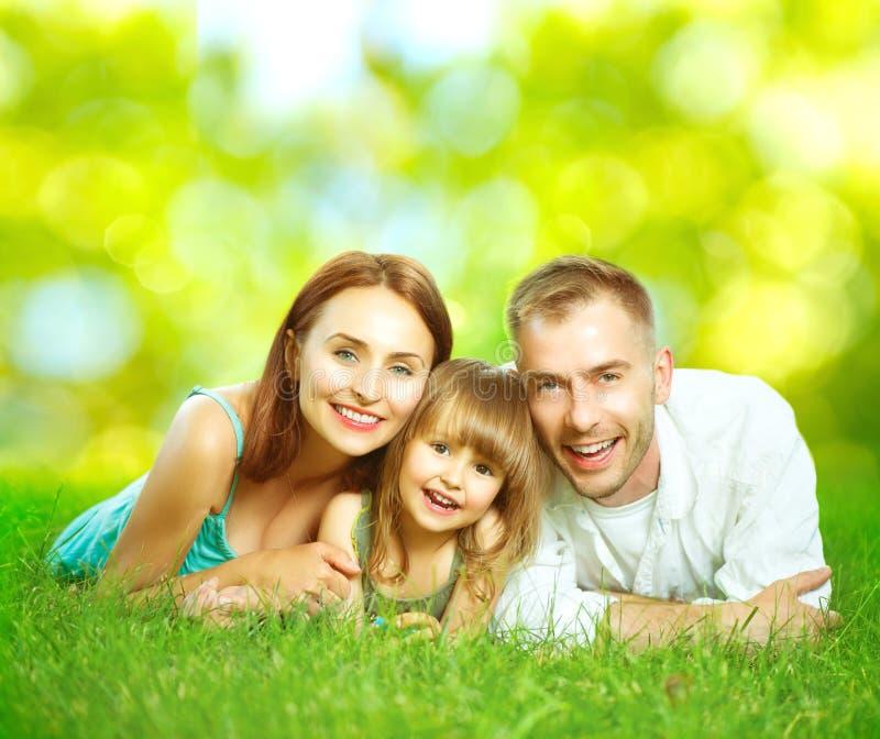 Gelukkige glimlachende jonge familie in openlucht stock afbeelding