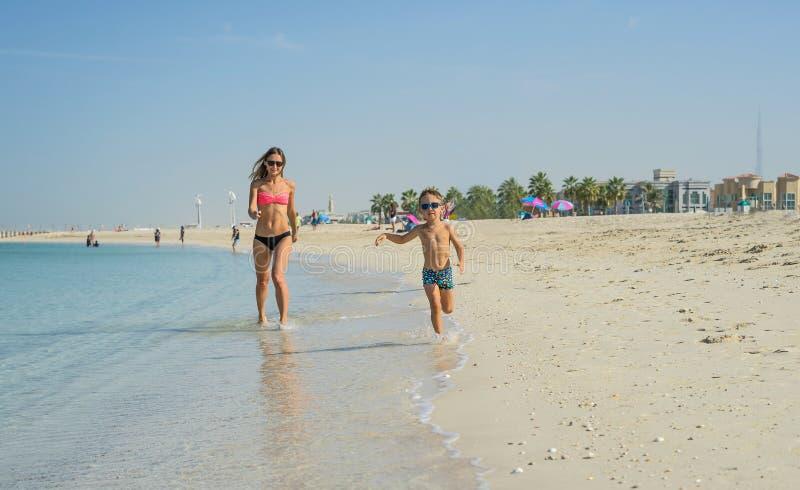 Gelukkige glimlachende jonge moeder en 5 éénjarigenzoon die op het strand van oceaan lopen, vakanties maken en van de zomer op st stock afbeeldingen