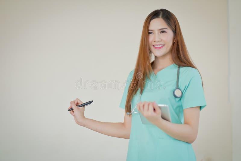 Gelukkige glimlachende jonge mooie vrouwelijke arts die leeg gebied F tonen stock foto