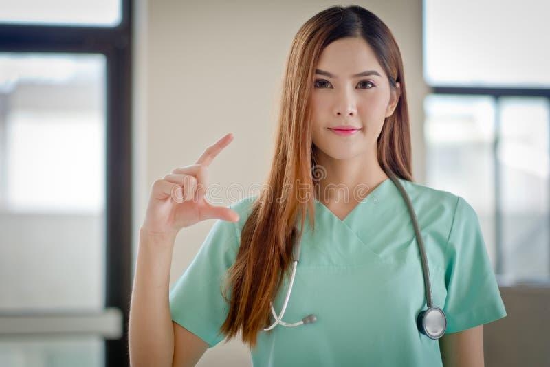Gelukkige glimlachende jonge mooie vrouwelijke arts die leeg gebied F tonen royalty-vrije stock fotografie