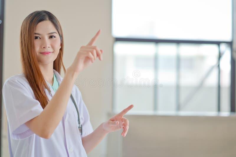 Gelukkige glimlachende jonge mooie vrouwelijke arts die leeg gebied F tonen royalty-vrije stock afbeelding