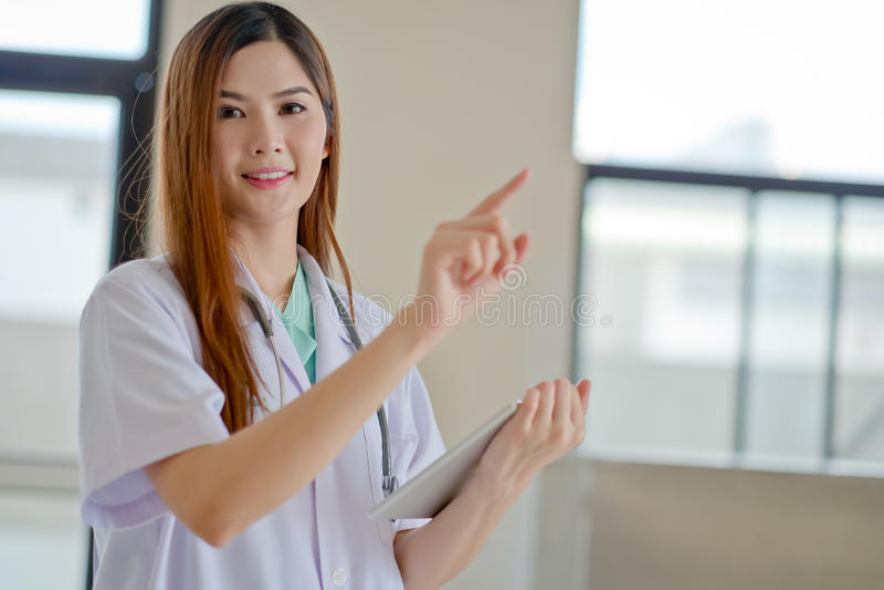 Gelukkige glimlachende jonge mooie vrouwelijke arts die leeg gebied F tonen stock afbeelding