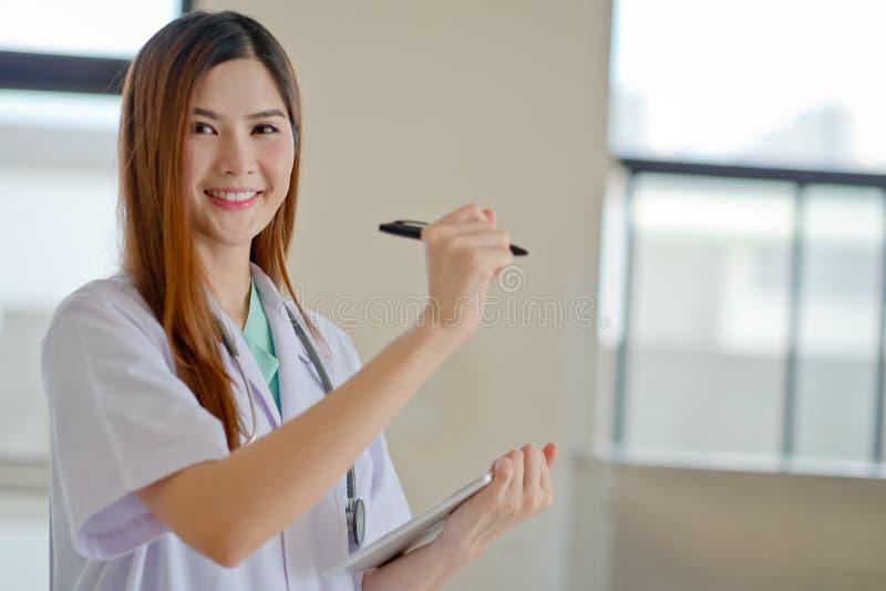 Gelukkige glimlachende jonge mooie vrouwelijke arts die leeg gebied F tonen stock foto's